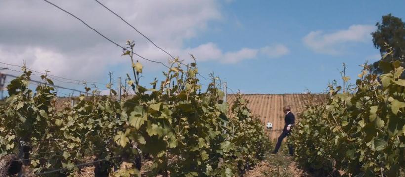 un homme en costume qui joue au foot dans les vignes