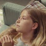 Une jeune adolescente blonde sur un canapé