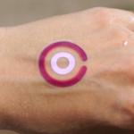 Une main avec un tatouage violet dessus.