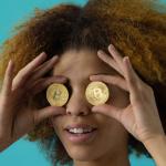 Une femme tient deux bitcoins au niveaux de ses yeux