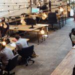 un open space avec des bureaux en bois et des guirlandes lumineuses