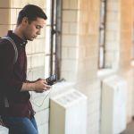 Une jeune homme consulte son smartphone à la pause entre deux cours