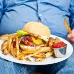 Un homme dans son canapé avec une bière et un burger
