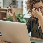 Une jeune femme métisse en train de s'énerver devant un ordinateur