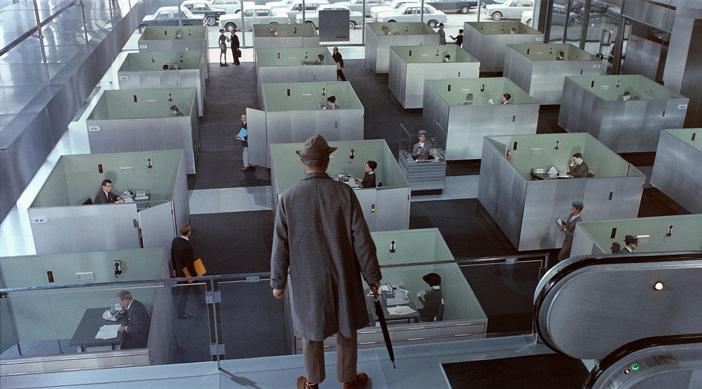 Dans une entreprise aux bureaux semi cloisonnés, un manager surveille ses équipes depuis la mezzanine