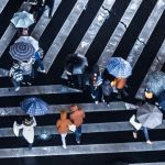 Une foule de gens traversant sur des passages piéton, avec des parapluies