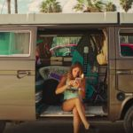Une femme regarde son téléphone dans son van
