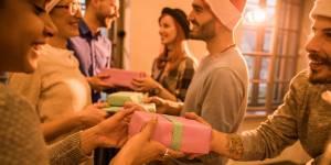 Des gens en train de s'échanger des cadeaux à une fête de Noël dans un bureau