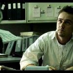un homme assis sur son bureau regarde son patron