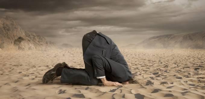 Un homme en costume enfonçant sa tête dans le sable