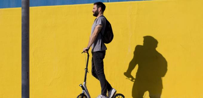 Un homme sur une trottinette devant un mur jaune