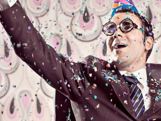 Un homme en train de faire la fête avec des paillettes à son bureau