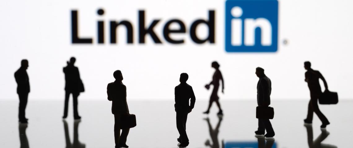 Des hommes et des femmes marchant devant le logo LinkedIn