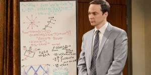 Sheldon Cooper, de la série Big Bang Theory, en costume devant un tableau
