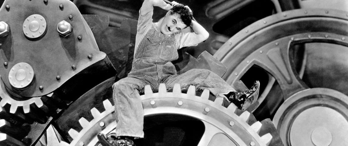 Charlie Chaplin dans Les Temps Modernes sur un rouage d'usine