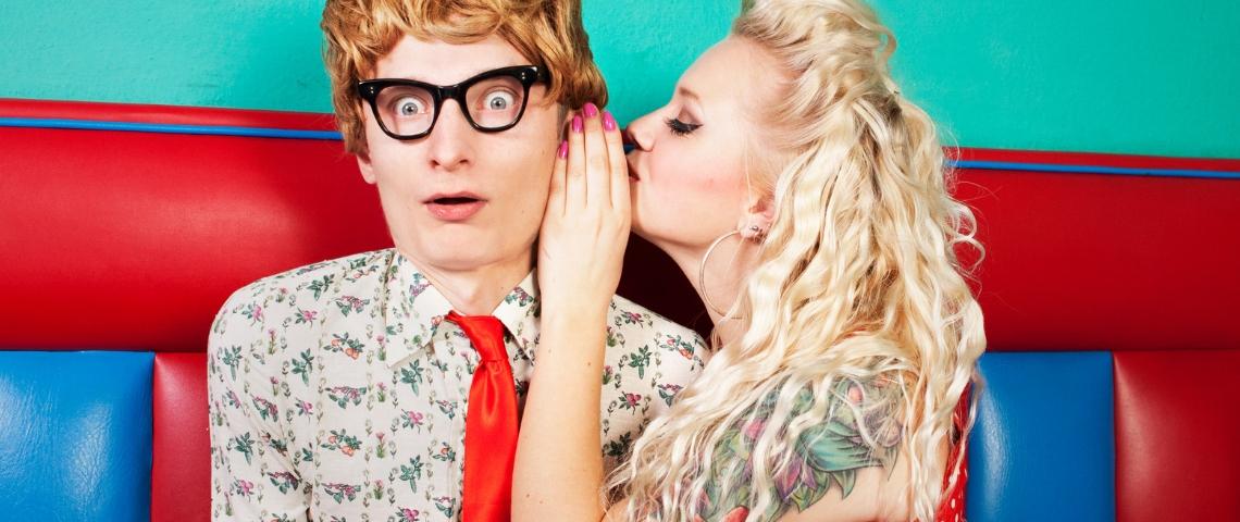 Une femme tatouée en train de dire un secret à un homme avec des lunettes