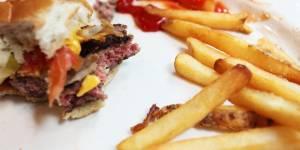 Un burger à moitié dévoré et des frites enduites de ketchup