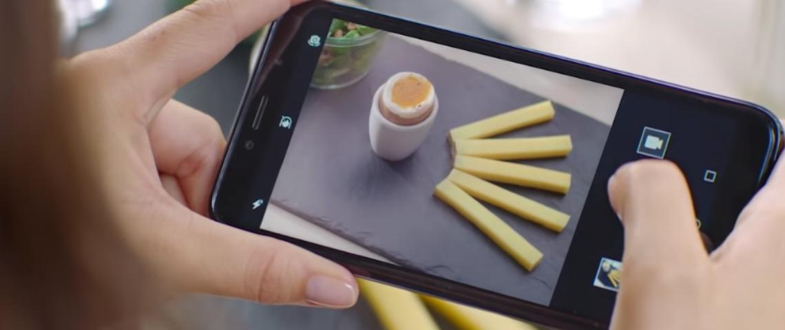Un smartphone qui prend la photo d'un oeuf à la coque avec des lamelles de comté