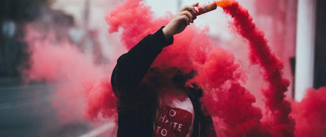 Un homme dans un sweat noir en train de propager un fumigène rouge