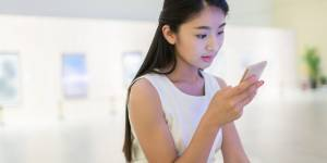 Une femme au musée, en train de regarder son téléphone portable