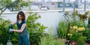 Une femme arrose des plantes dans un jardin sur des toits