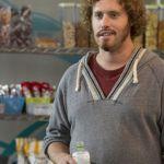 Erlich Bachman, dans la série Silicon Valley, en train de boire une boisson devant un stand de nourriture