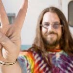 Un hippie devant une caravane en train de faire le signe peace