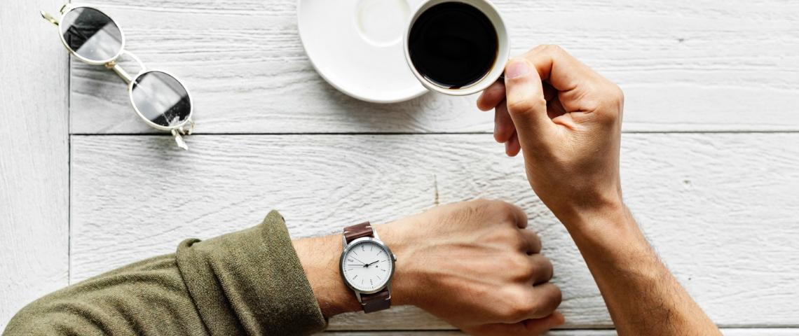 Une main d'homme avec une montre et un café