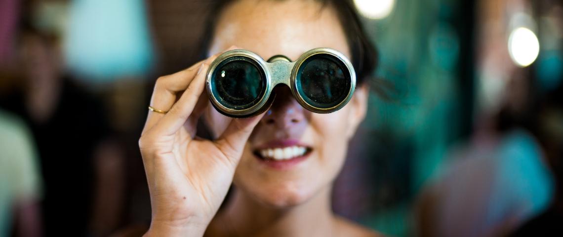 Une femme qui regarde à travers des jumelles