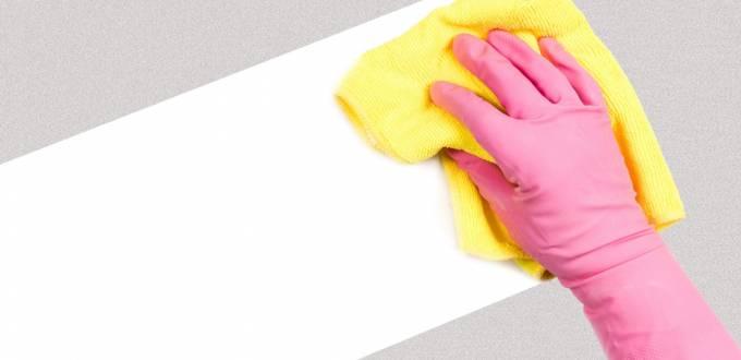 Un main avec un gant en latex qui fait le ménage