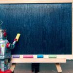 un robot devant un tableau noir