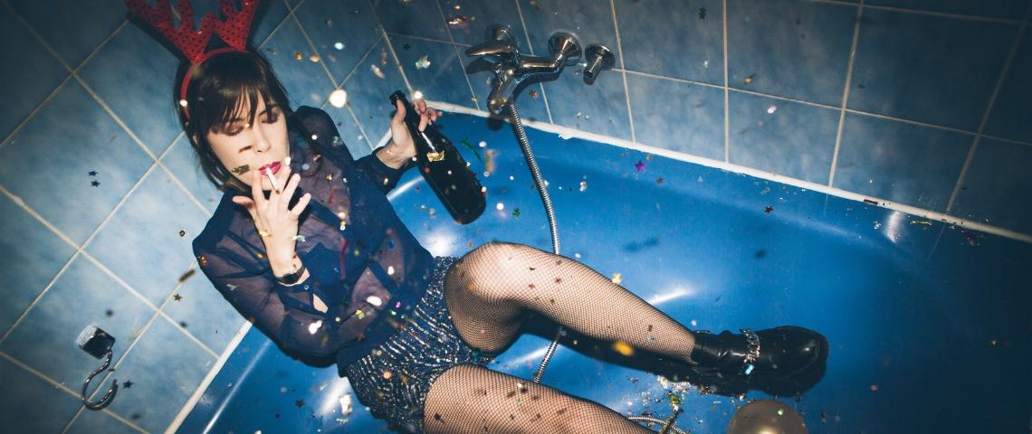 Une femme boit et fume dans une baignoire
