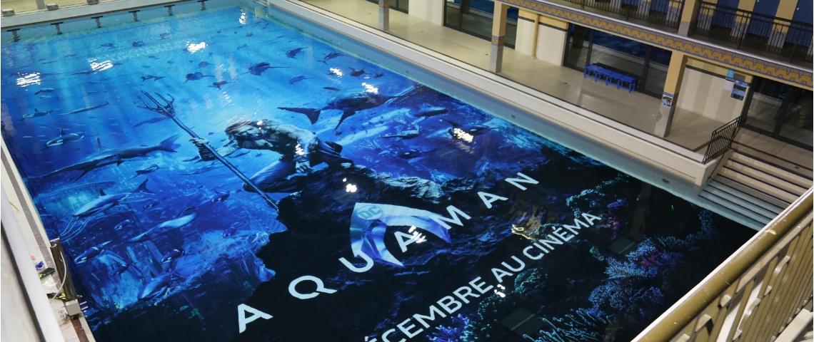 La piscine Pailleron avec l'affiche d'Aquaman au fond