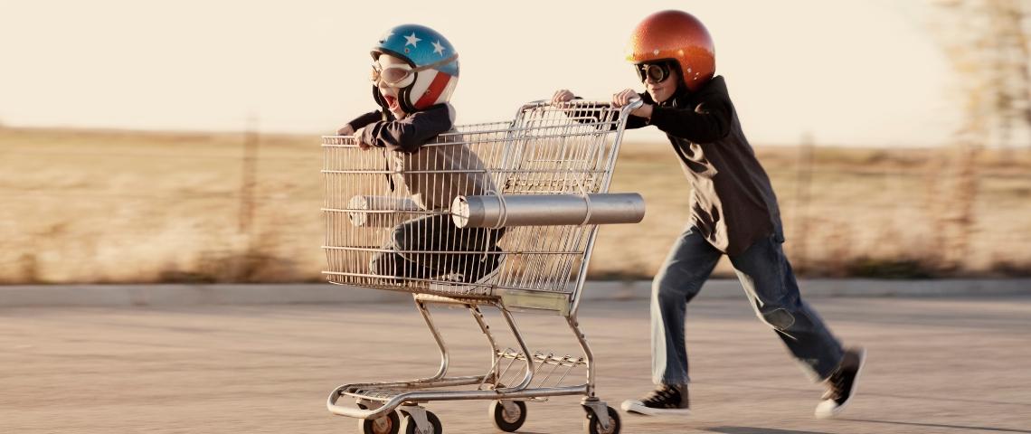 Deux enfants avec un chariot de supermarché