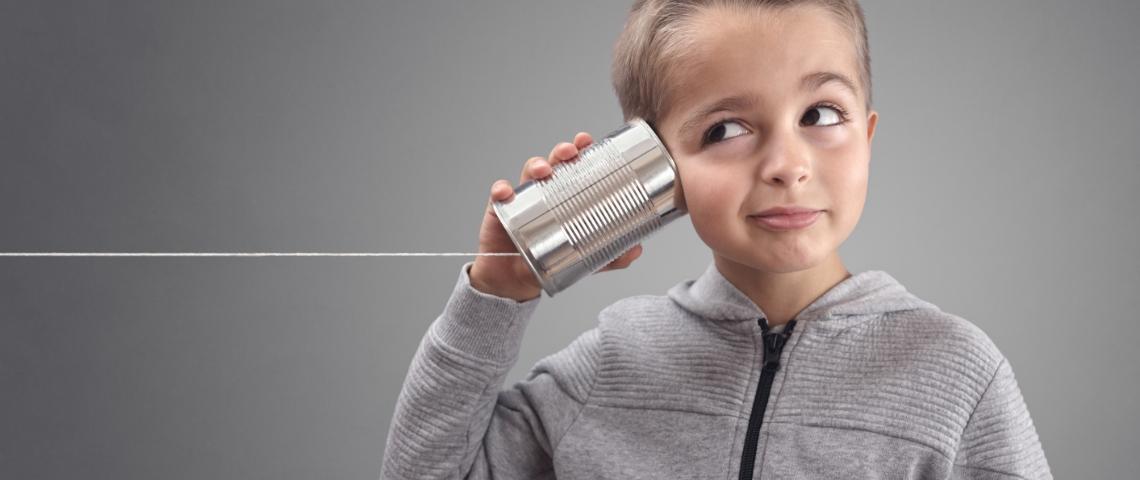 Un enfant avec une boîte de conserve sur l'oreille