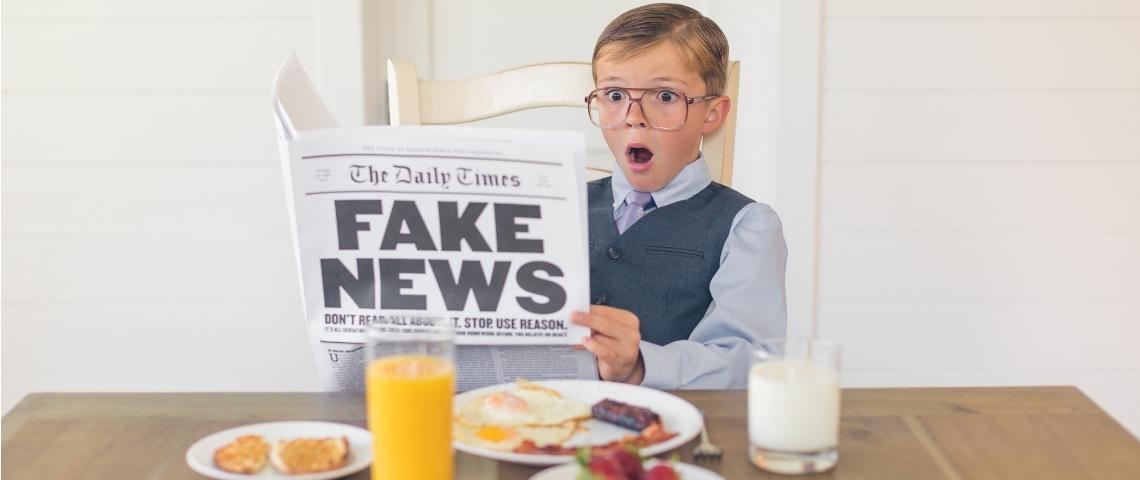 un enfant étrange lit le journal le matin au petit déjeuner