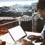 une femme noire tape sur son ordinateur sur un balcon