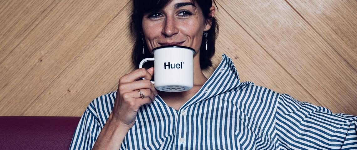Une femme qui boit dans une tasse avec écrit Huel