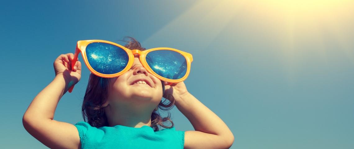 une petite fille avec des lunettes bleues