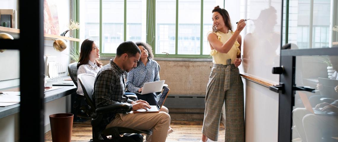 une femme forme ses collègues en petit groupe