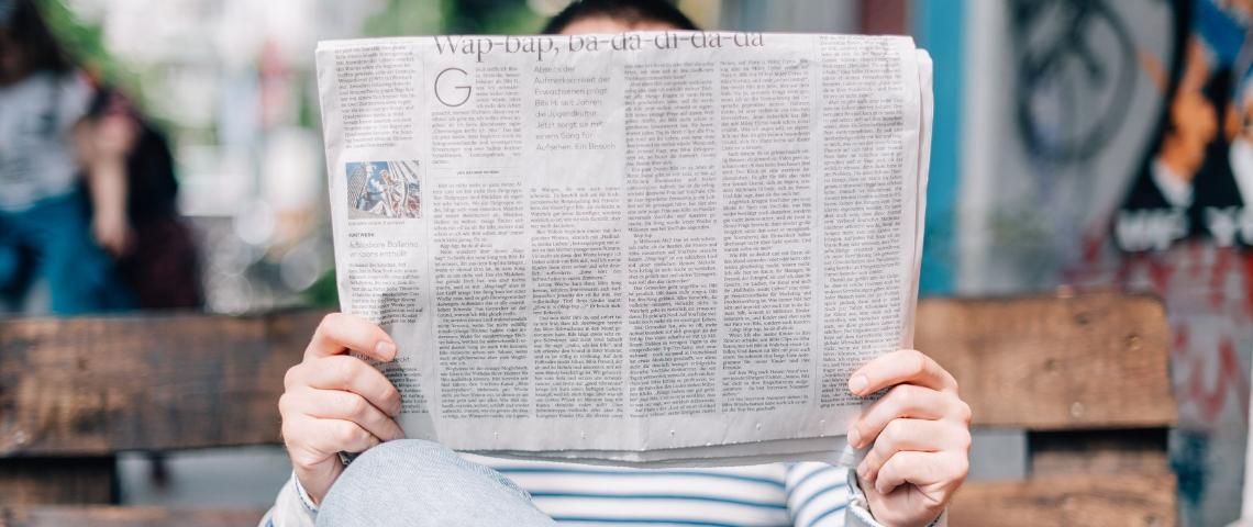 Un homme qui lit un journal papier