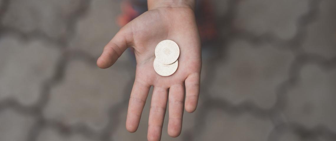 Une main tendue avec une pièce de monnaie