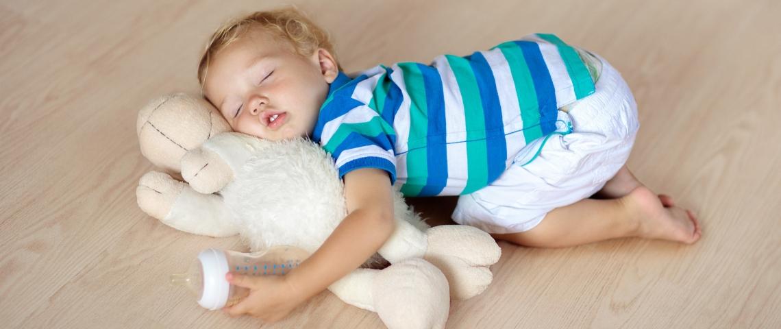 Un enfant qui dort avec sa peluche