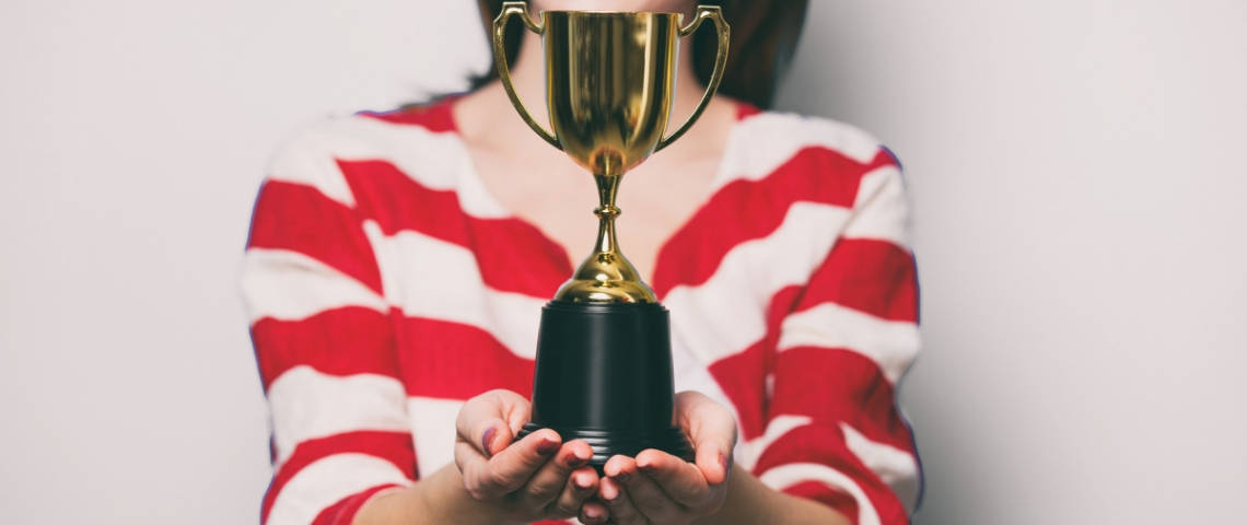 Une femme avec un t-shirt rayé qui tient un trophée