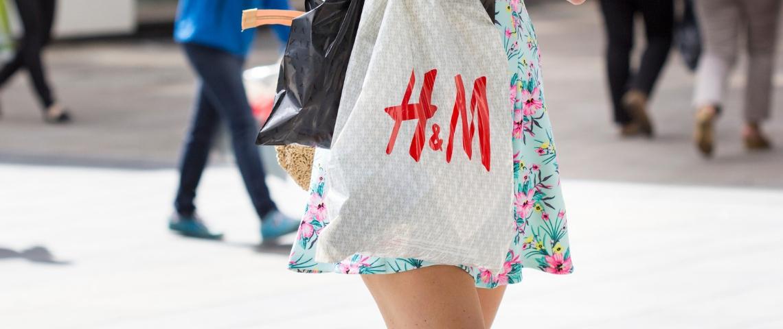 Une jeune femme en robe portant un sac H&M dans la rue