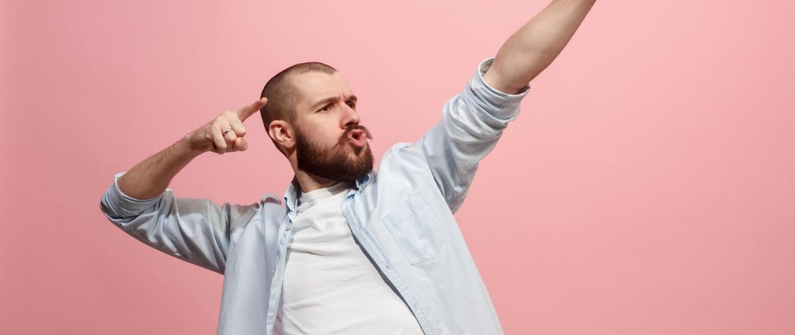 Un homme en train de faire une power pose sur un fond rose