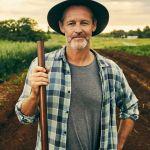 Un agriculteur portant un chapeau et une chemise à carreau, tenant une fourche, dans un champ