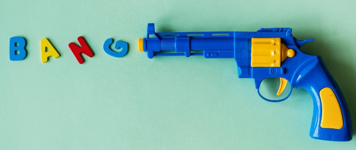 Un pistolet en plastique avec des lettres BANG