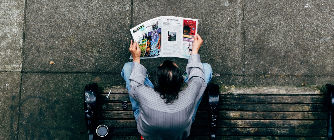 Un homme qui lit un magazine papier