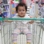 Une petite fille brune au milieu d'un supermarché